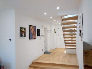 Gallery-style arrangement of pictures, in the entrance of a home in Oxshott.