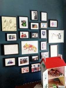 24 pictures hung lo, behind a doll's house, in a playroom in Plumpton, East Sussex