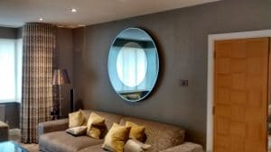 A large round mirror hung in a living room above a sofa in Seaford.