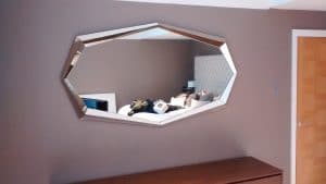 Octagonal large mirror hung above chest of drawers in a home in Lewes.