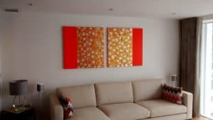 A pair of bright abstract canvases hung above a sofa in a living room.