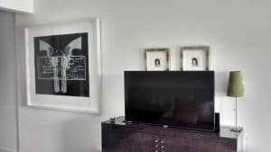 Arranging the space around a TV. A large graphic print, similar in size and colour, serves to balance the black rectangle. Two petite portraits peep over, providing some relief from the dominant shapes.