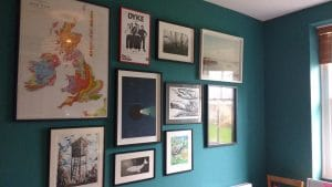 Collage style hang of framed pictures on an aquamarine wall in a basement room in Brighton