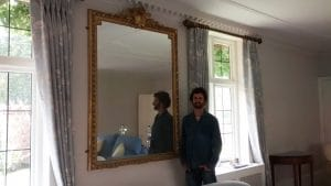 Reflecting on a successful mirror hang. A Neo-Classic gold gilt pane mirror hung between windows in a living room in Hampshire.