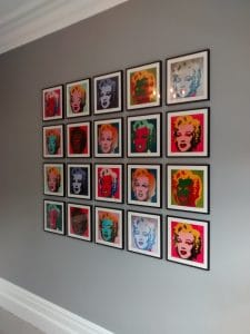 A picture wall of twenty Andy Warhol prints, hung in a grid.