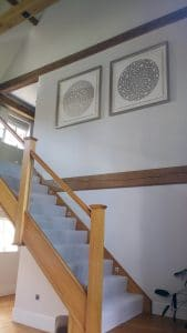 Two large square prints high above a staircase in Dunmow.