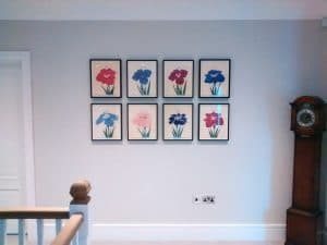 Eight Japanese flower pictures hung in a grid formation.