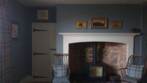 Three small artworks installed above a large hearth in a country cottage in Faversham.