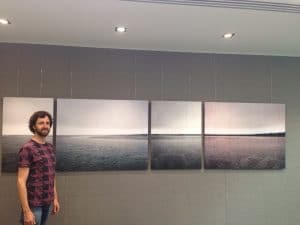 No marks. A panoramic seascape suspended with transparent chords off a picture rail. Hung it more horizontal than the horizon itself.