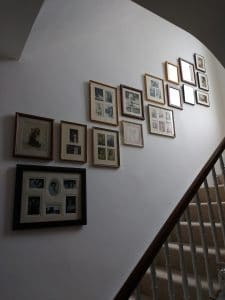 A sepia themed photo collage wall runnning above stairs in a home in Richmond.