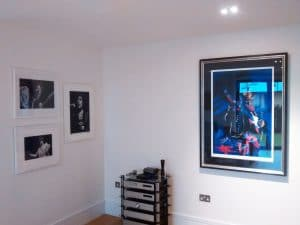 A corner of a room showing four pictures of musicians hung