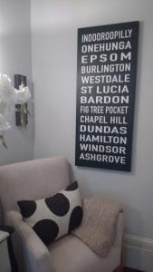 A rectangular print of thirteen addresses hung above an armchair.