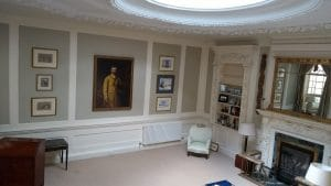 An ancestral portrait and Victorian prints hung in a skylit basement drawing room in Chelsea, London.