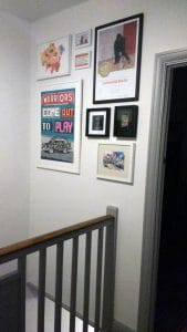 Eight various sized pictures arranged together to creating a square shape, above stairs in a home in Bromley, Kent.