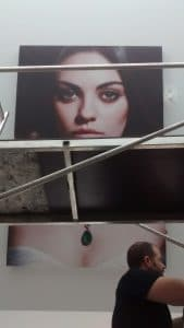 Large Mila Kunis poster hanging on a slanted ceiling in Mayfair, London.
