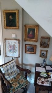 Six gold framed pictures hung in a small sloped ceilinged space in Little Coxwell, Oxfordshire.
