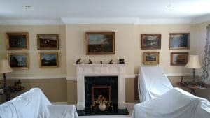 A statement wall of gold framed oil paintings hung in a living room in Little Coxwell, Faringdon, Oxfordshire.