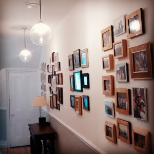 Picture wall ideas. A collage of over 50 framed photographs in a hallway in Putney