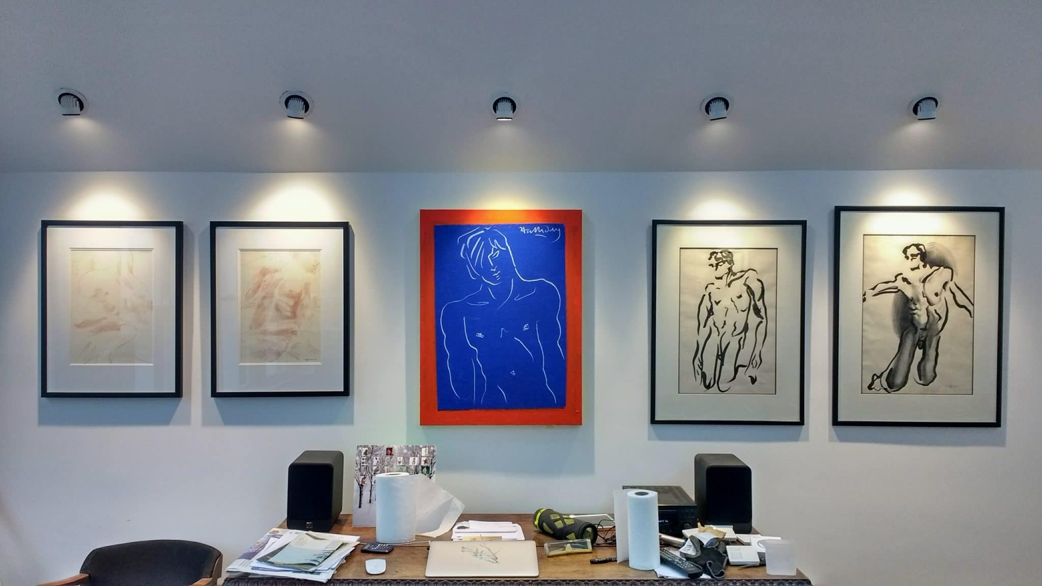 A gallery install of male nudes, hung above a desk in Horsham. in-built spotlighting means business.