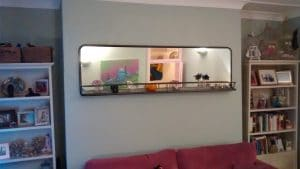 Large Modern horizontal pane mirror with nifty built-in shelf, hung in a living room.