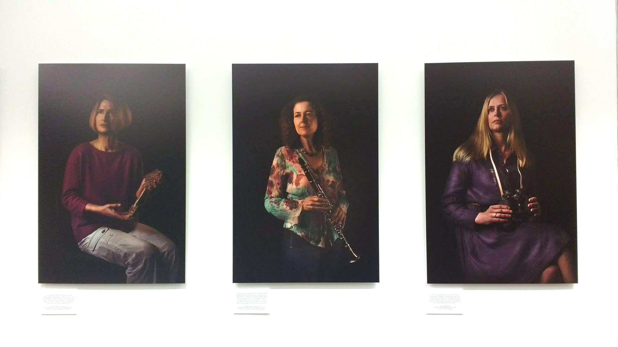 Twelve Women in Academia - a series of photographs printed on aluminium, by artist Miss Aniela. Twelve female academics depicted in the 17th century sober, still life manner, each holding an object significant to them. Installed at The University of Sussex and exhibited in the library on campus in Falmer