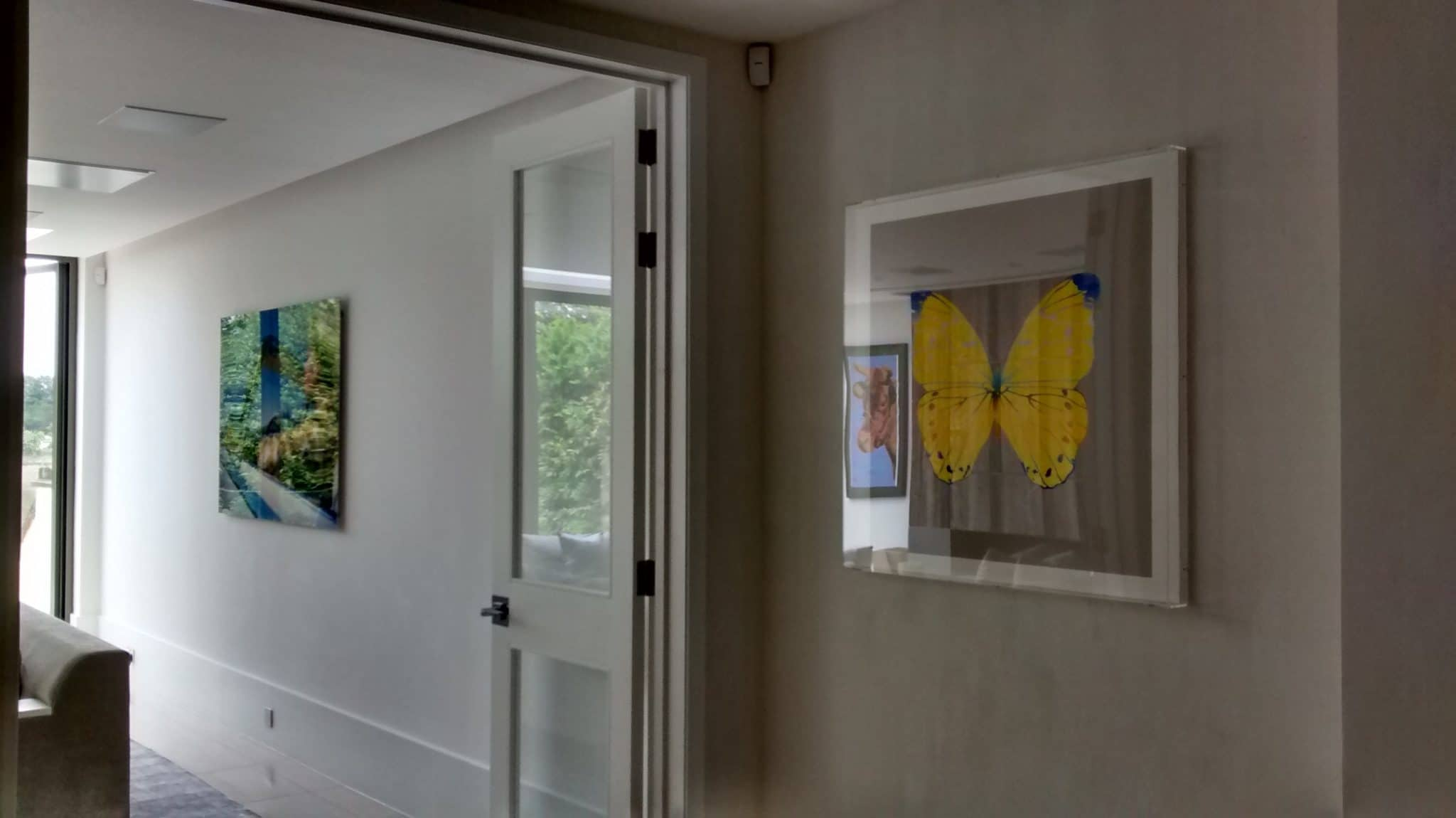 Two similarly sized square pictures, helps the space divided by the doorway flow, creating a more united living space in Horsham.
