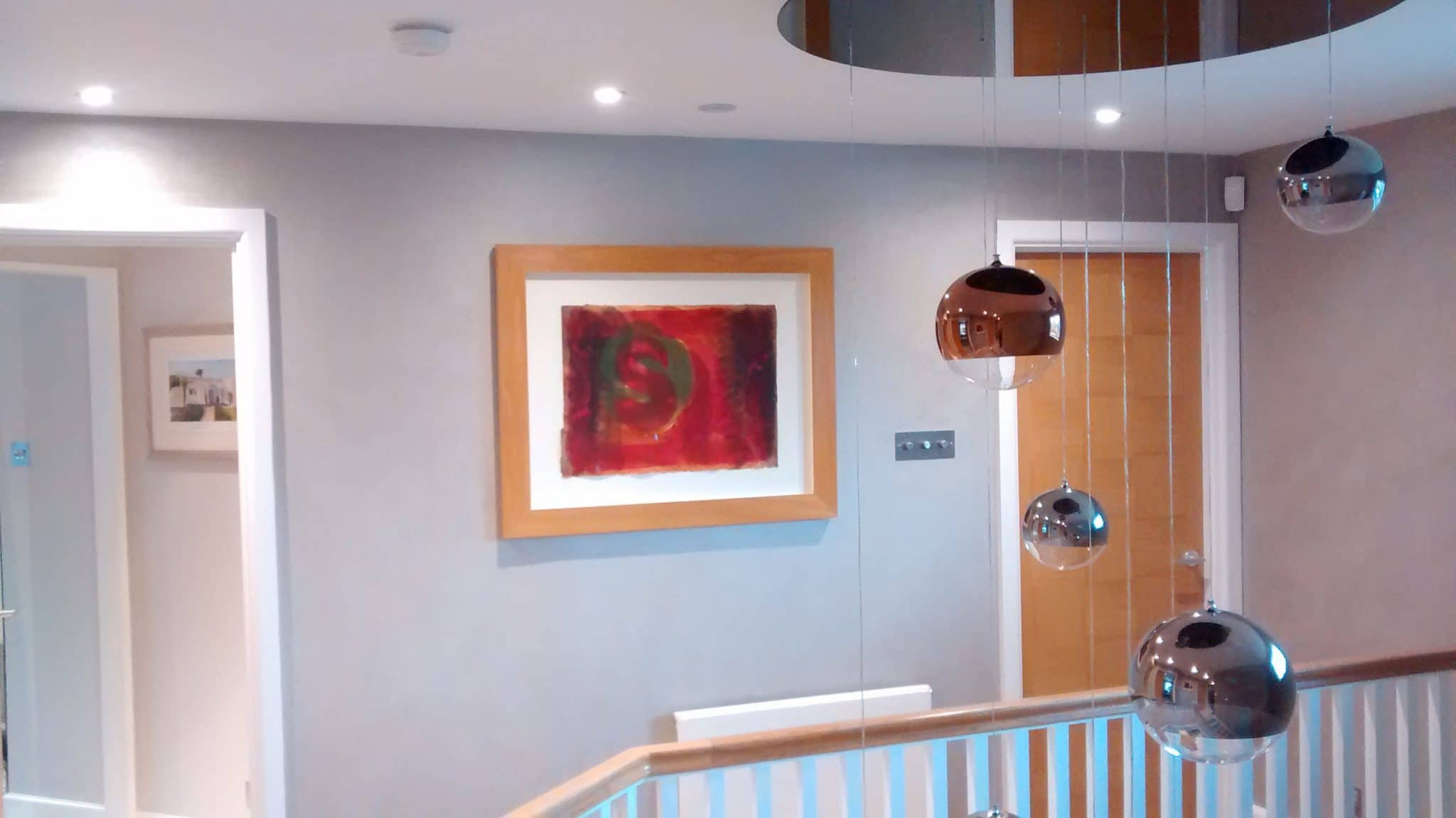 Timber framed picture hung in the stairwell landing of a home in Burgess Hill.