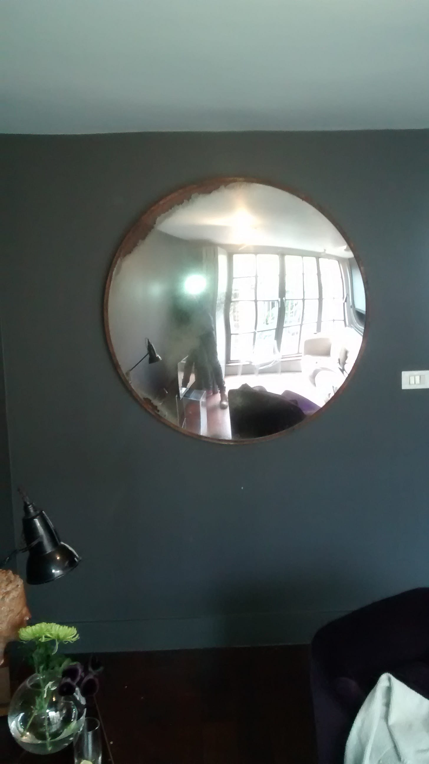 A 30kg circular and convex metal framed mirror hung high above a sofa in a living room in East London.