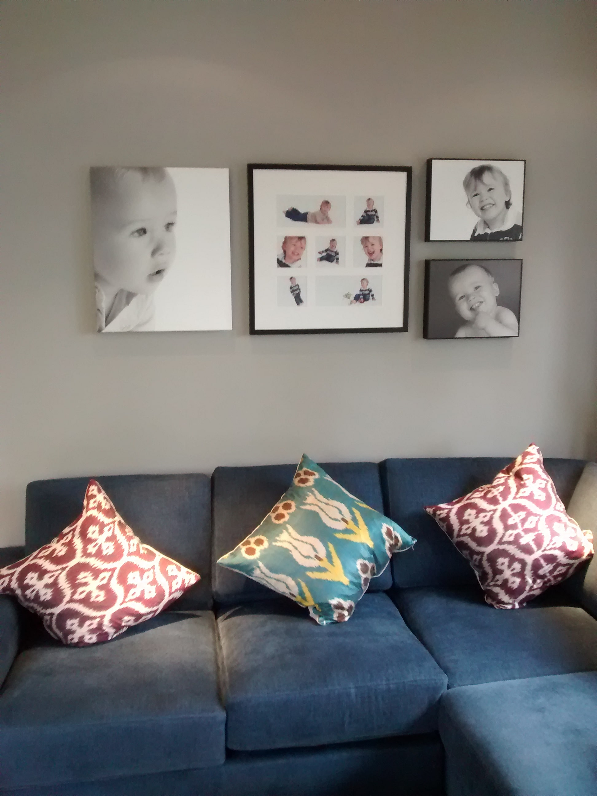 Family photos hung in an Eastbourne living room, above the sofa.