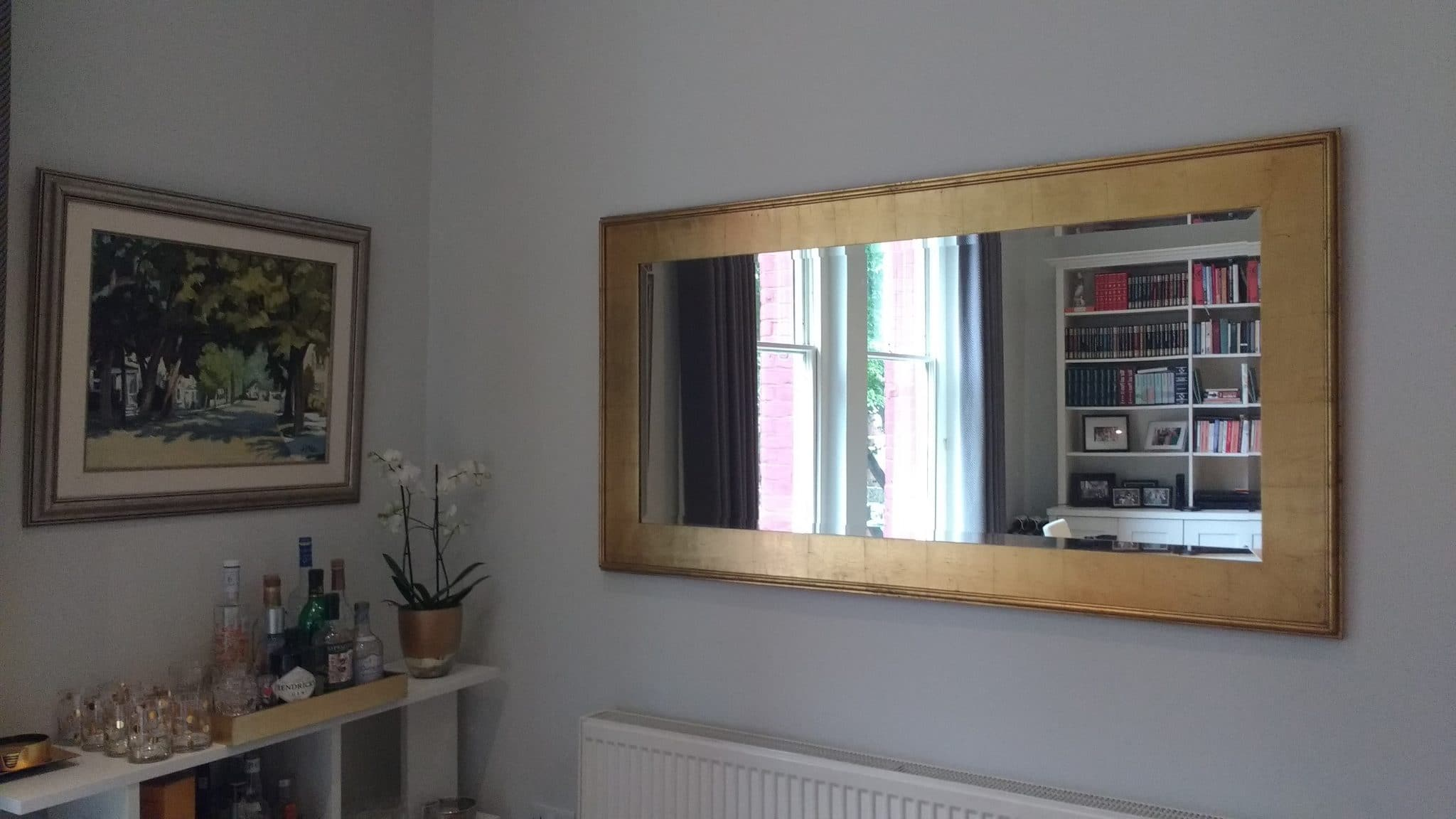 A gold framed rectangular mirror installed in a home in Marleybone/