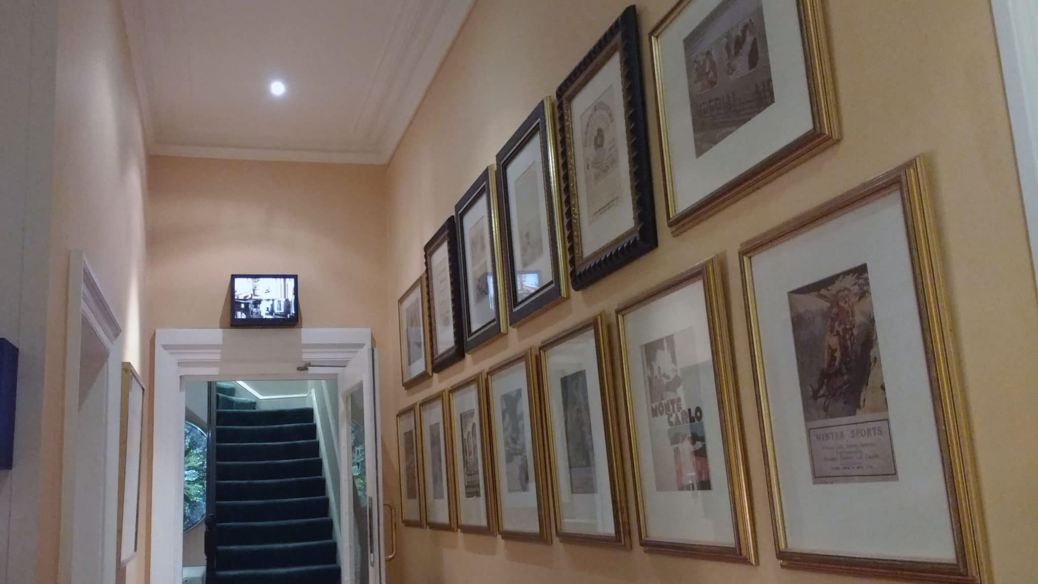 A picture wall of thirteen framed pictures hung in rows and secured with security fixings in a corridor in a hotel in Bath