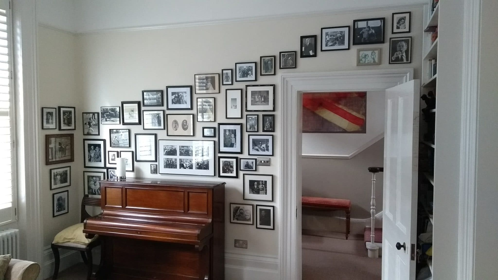 A cascading collage wall of phtotographs framing a door and piano.