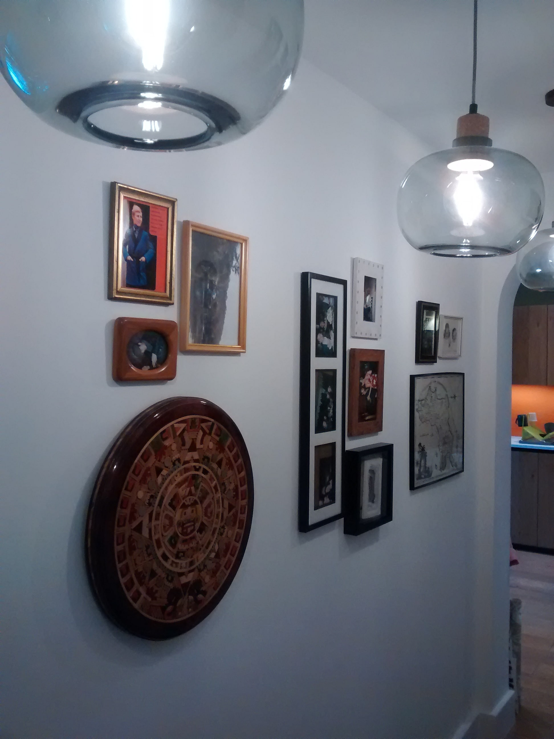 A collage wall of various sized and coloured objects hung in a narrow hallway in a home in Hampstead, London