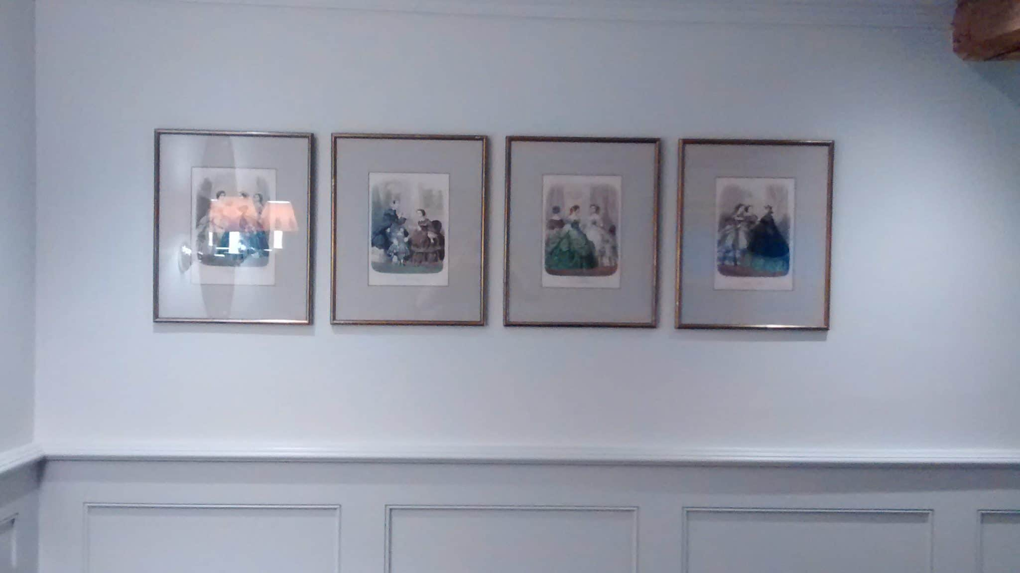a row of Victorian watercolours in a duck egg hallway in Burford, Oxford.