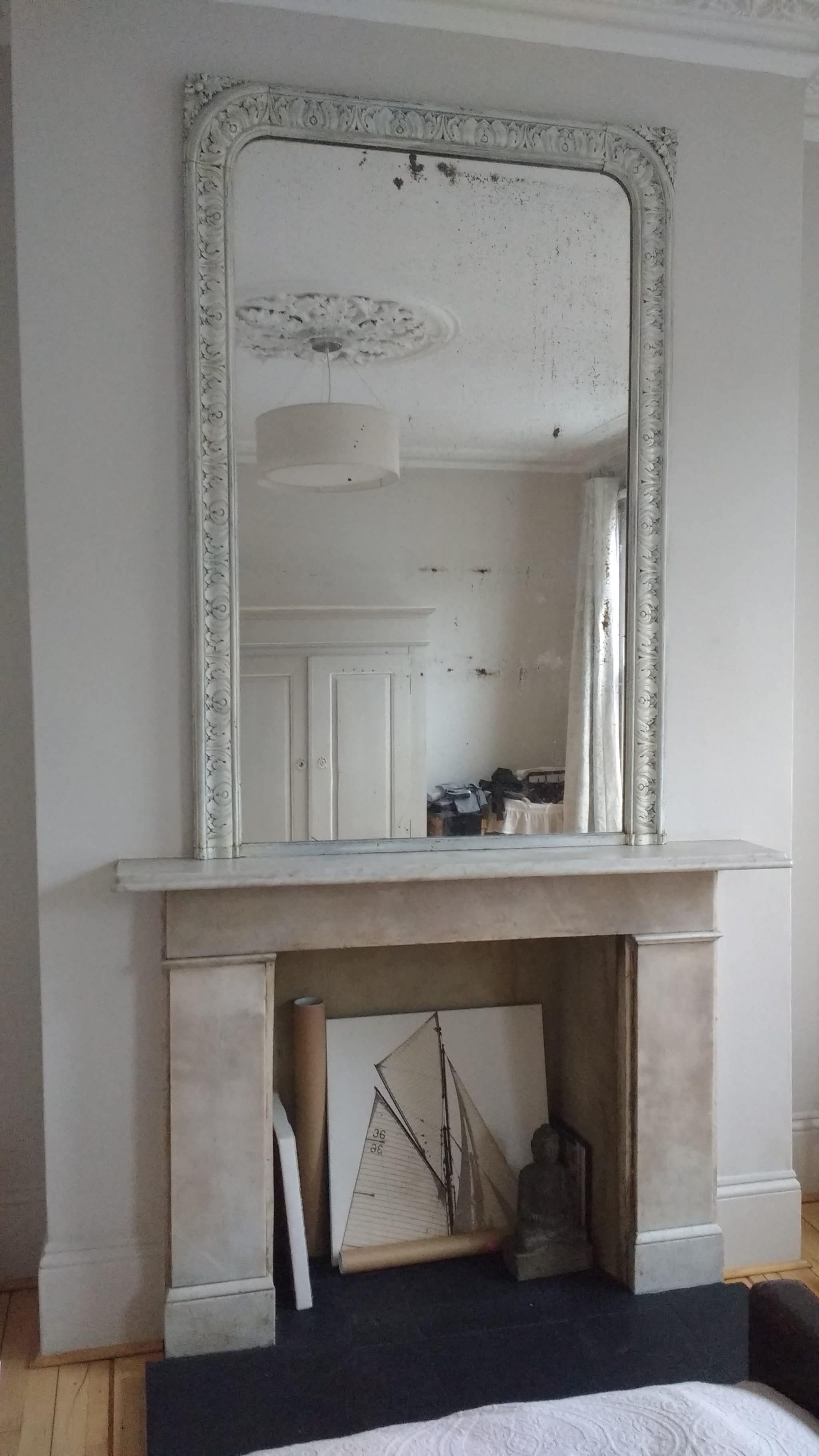 Leaning large mirror above a fireplace in a bedroom in Ladbroke Grove.