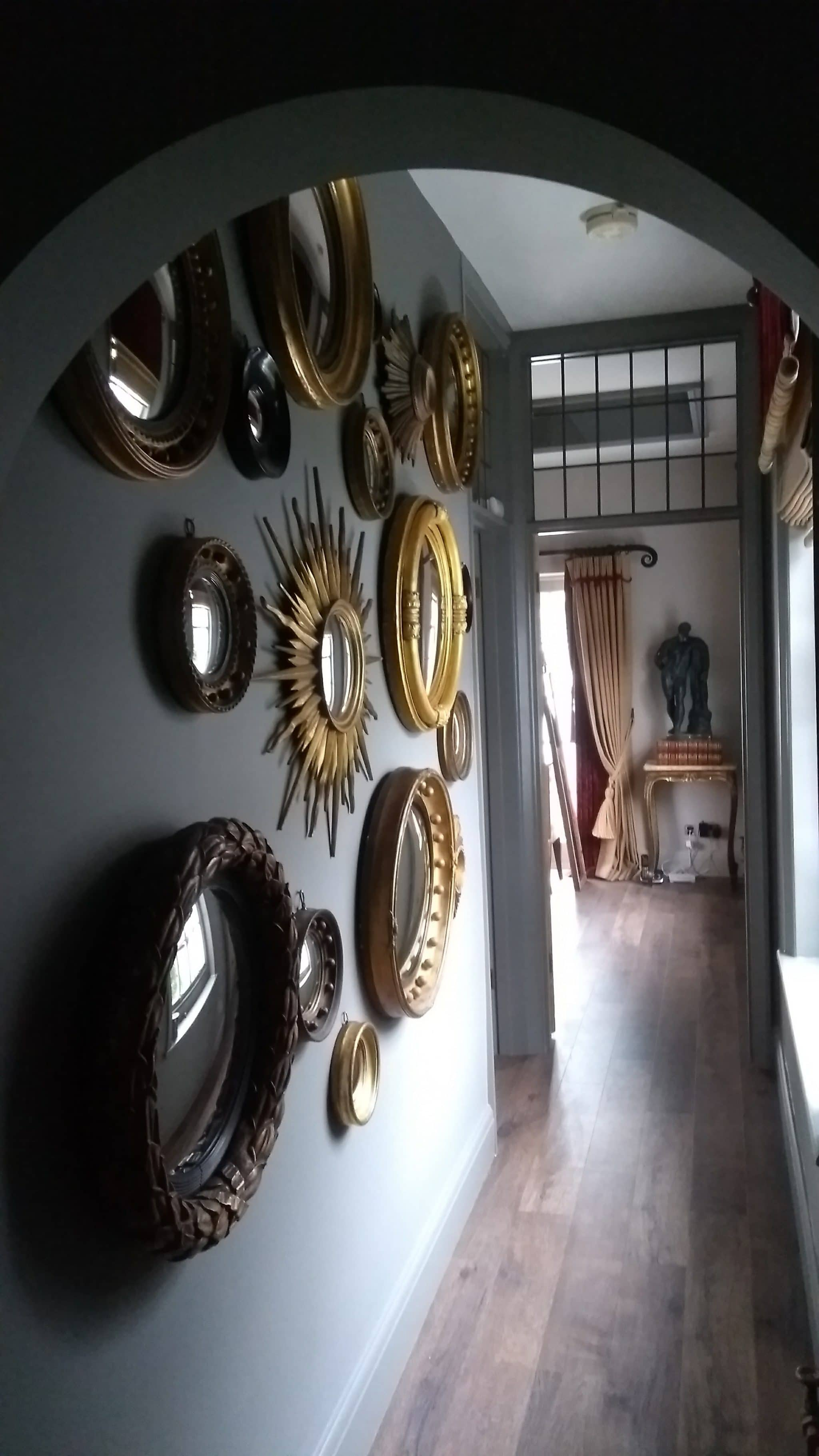 Brass and gold gilded convex mirrors hanging in a hallway in Brighton.