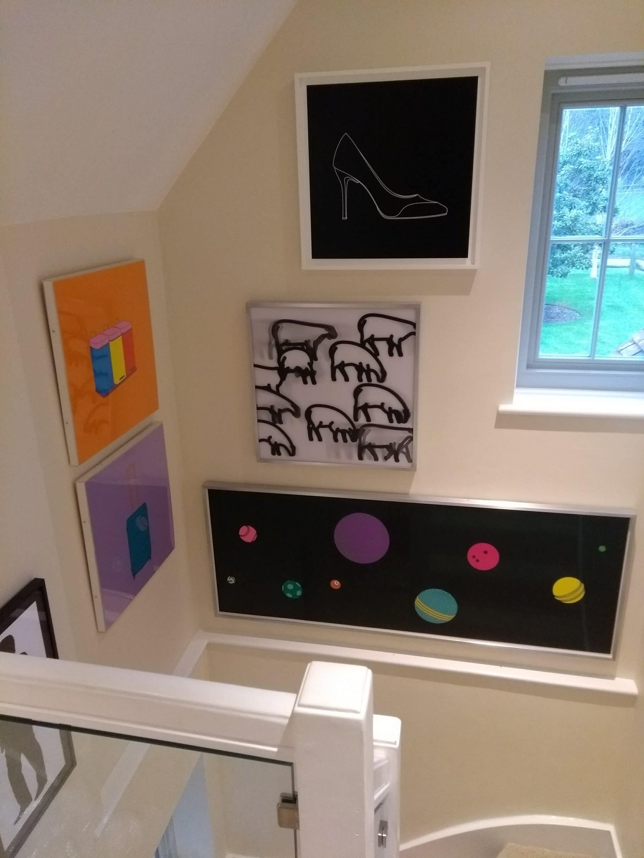 Julian Opie and Michael Craig-Martin paintings hung in a stairwell in Haywards Heath.