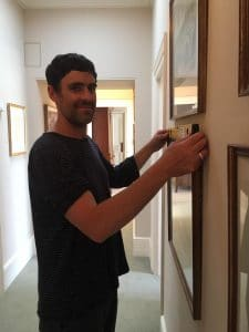Jesse Wade hanging a grid of pictures in a client's hallway - St Albans, Hertfordshire